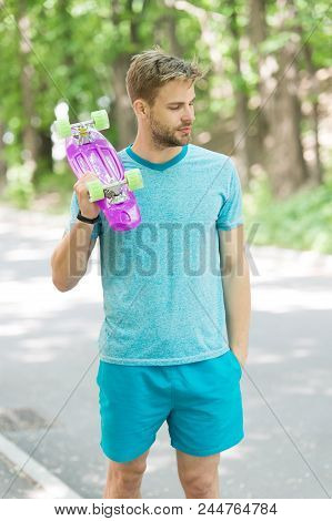 Still Childish. Man Calm Face Carries Penny Board Park Nature Background, Defocused. Guy Carries Pen