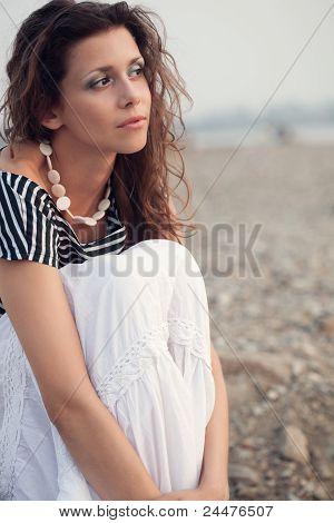pensive brunette woman sitting on coast