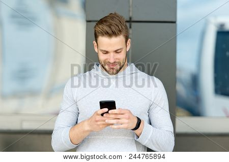 Staying In Touch. Man With Beard Walks With Smartphone, Urban Background. Guy Use Smartphone To Send