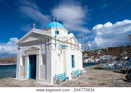 Agios Nikolaos Church In Mykonos, Greece. Temple Building With Blue Dome On Sea Quay. Church On Sunn