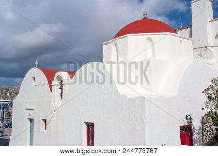 White Church In Mykonos, Greece. Church With Red Dome On Cloudy Blue Sky. Chapel Building Architectu