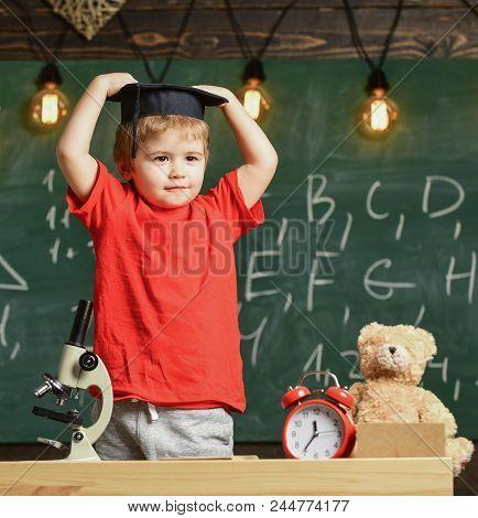 Kid Boy In Graduate Cap Ready To Go To School, Chalkboard On Background. Kindergarten Graduation Con