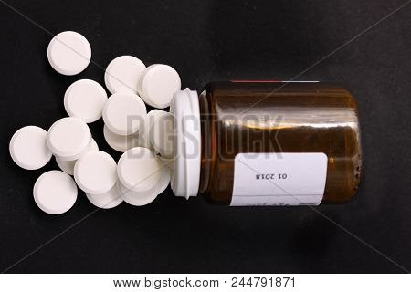 White Pills Spilled From Fallen Pill Bottle. Pills And Medicine Container Lying On Black Background