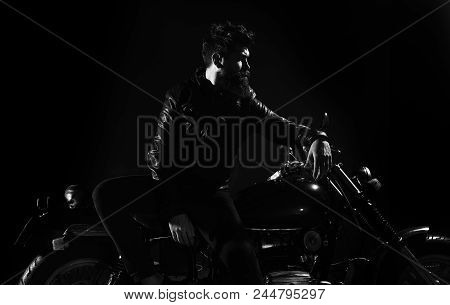 Brutality and masculine concept. Macho, brutal biker in leather jacket stand near motorcycle at night time. Man with beard, biker in leather jacket lean on motor bike in darkness, black background. poster