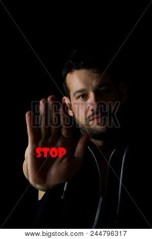 A Dark Photo Of A Young Man Doing A Gesture With Meaning Already Enough.a Young Man Holds His Hand I