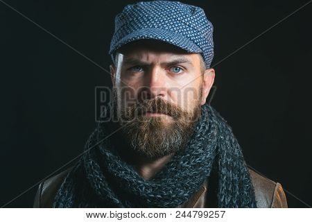Attractive Bearded Man Dressed In Leather Jacket, Cap And Scarf Wrapped Around His Neck. Handsome Ma