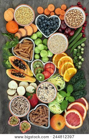 High fibre health food concept with whole wheat pasta, legumes, cereals, grains, fresh fruit & vegetables on marble background top view. Foods high in omega 3, antioxidants  & smart carbohydrates.