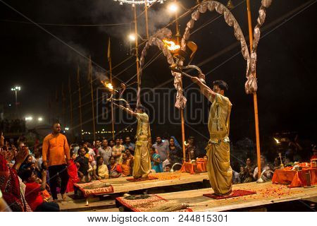 VARANASI, INDIA - MAR 15, 2018: Group of priests perform Agni Pooja (Sanskrit- Worship of Fire) on Dashashwamedh Ghat - main and oldest ghat of Varanasi located on the Ganges.