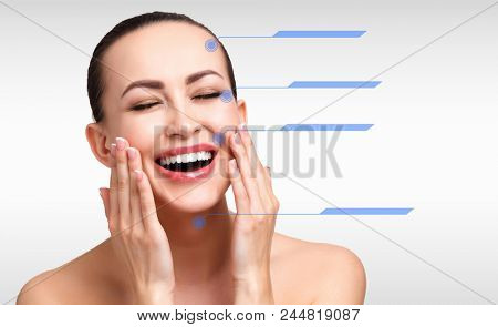 Closeup shot of female pretty face with blue marks on skin for cosmetic medical procedures, grey steel background