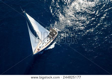 Sailboat while cruising / sailing at opened sea. Yacht with full sails up at the end of windy day. Sailing theme - aerial / drone background. Yachting background design.