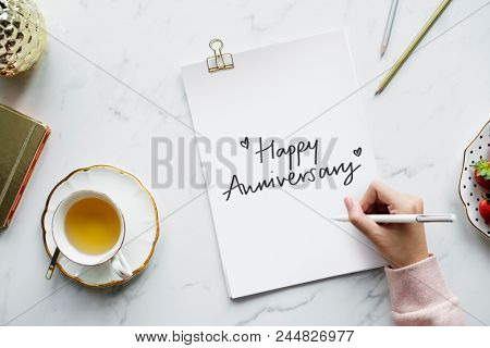 Woman writing a Happy Anniversary card