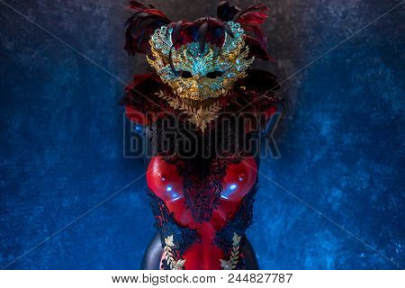 Festival Red golden venetian carnival mask with feathers  on a draped red velvet theater curtain. Mask in the dark