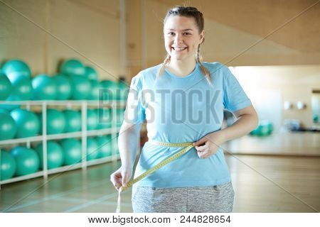 Happy young chubby female measuring her waist after training in fitness center
