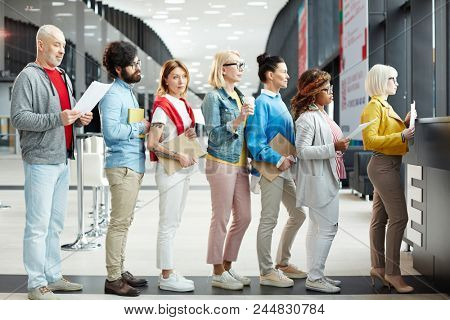 Group of modern multiethnic people of different ages wearing casual clothing holding papers and sketchpads while standing in long line for registration