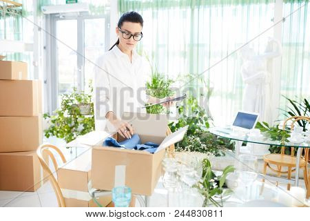 Serious confident attractive young female entrepreneur viewing delivered goods and unpacking box while preparing restaurant for opening
