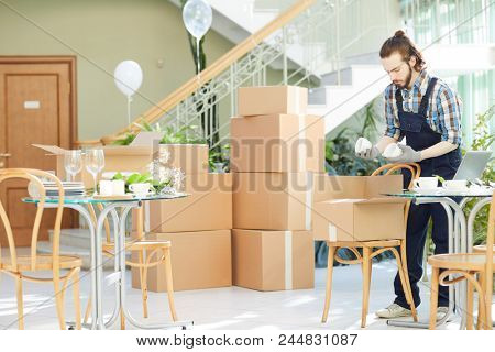 Concentrated handsome young logistics company mover in uniform unpacking box and checking cups while working at place of delivery