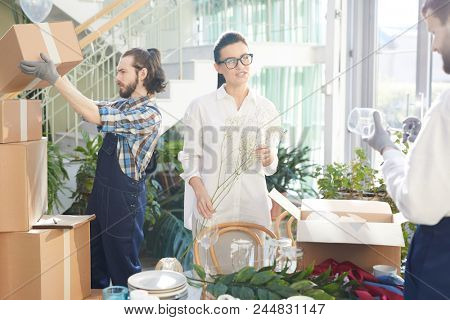 Positive confident female interior designer in glasses holding twig while talking to mover while they unpacking boxes and examining goods in space full of plants