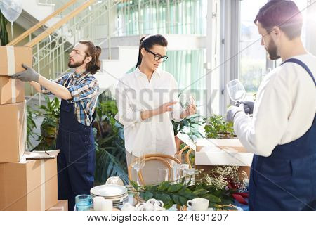 Serious confident female restaurateur in glasses checking wineglass while unpacking boxes delivered by movers, handsome bearded worker in gloves stacking boxes