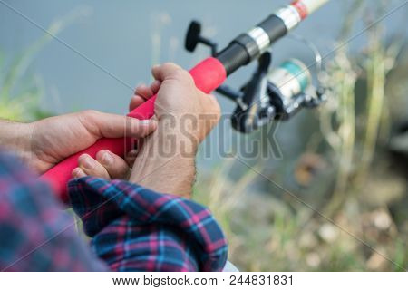 Man fishing at river bank, summer outdoor. Summer leisure, hobby. Fishing. Angling. Man's hand with fishing rod over light green lake water with copyspace.