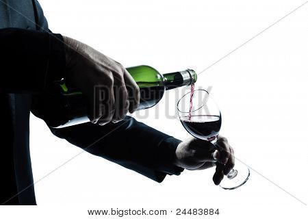 one caucasian man hands detail pouring red wine in a glass silhouette in studio isolated white background