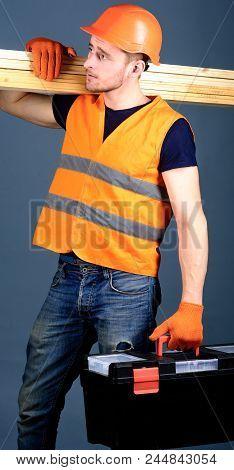 Carpenter, Woodworker, Labourer, Builder On Calm Face Carries Wooden Beams On Shoulder. Woodworking