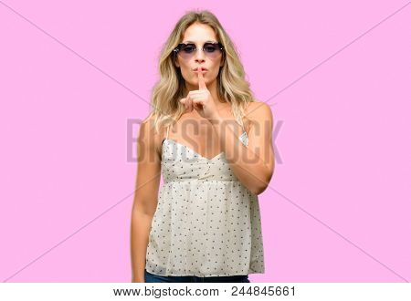 Young woman wearing sunglasses with heart shape with index finger on lips, ask to be quiet. Silence and secret concept