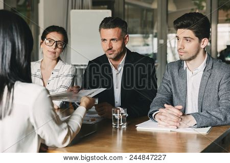 Business, career and placement concept - three executive directors or head managers sitting at table in office and examining resume of female worker poster