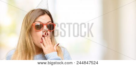 Young woman celebrates birthday covers mouth in shock, looks shy, expressing silence and mistake concepts, scared