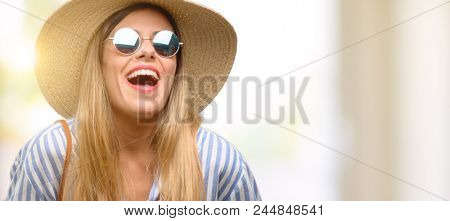 Young woman wearing sunglasses and summer hat confident and happy with a big natural smile laughing
