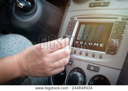 Driver using knob to adjust volume in the car audio system