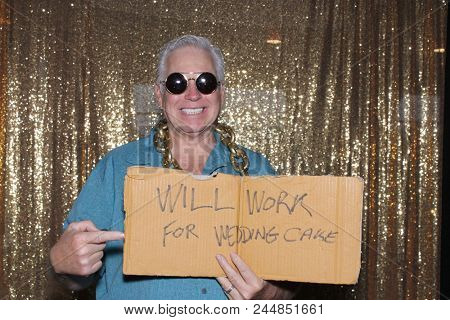 A happy middle aged man in a Photo Booth.   A happy man laughs, holds a cardboard sign that reads WILL WORK FOR WEDDING CAKE as he smiles while in a Photo booth at a Party. Party Time Photo Booth.