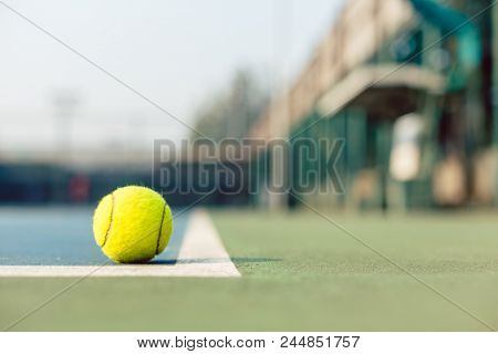 High-angle close-up of a fluorescent yellow tennis ball in the corner at the baseline on the blue acrylic surface of the tennis court