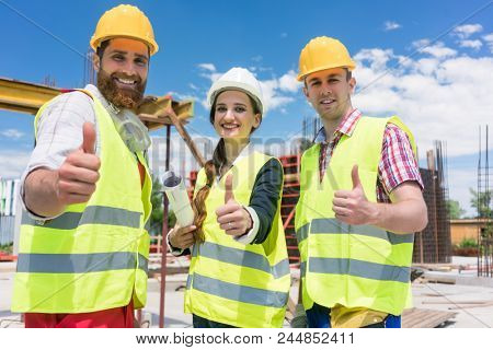 Portrait of three cheerful colleagues in a construction team looking at camera, while showing thumbs up as a gesture of agreement and confidence during work in progress