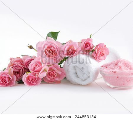 Set of pink rose and rolled, towel ,salt in spoon on mat