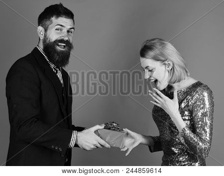 Boyfriend Gives Gift To His Girlfriend. Couple In Love Shares Presents On Red Background. Relationsh