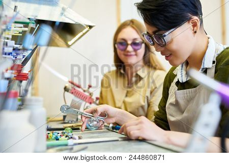 Side View Portrait Of Two Modern Female Artists Working With Glass, Focus On Ypung Asian Woman In Gl