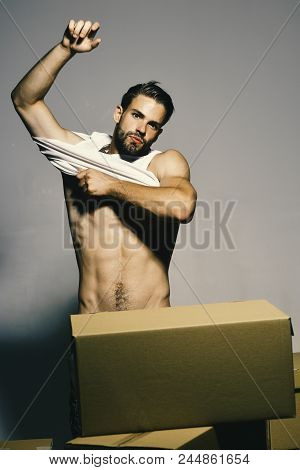 Guy With Naked Torso Holds Stands Naked Behind Boxes. Man With Sexy Torso Stands On Dark Grey Backgr