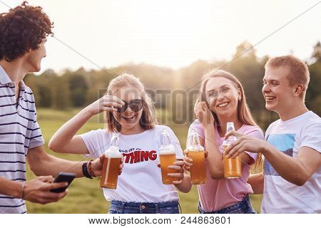 Summer time and leisure concept. Happy girls laugh at boy`s funny jokes, drink cold beverages, have cheerful expressions, spend spare time on summer field. Companionship and relationship concept poster