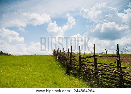 Rural Summer Landscape With Fence And Blue Sky