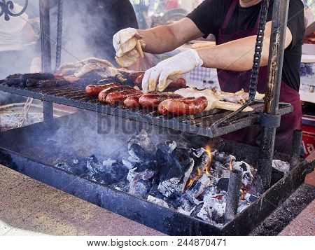 Cook Cooking Sausages, Bacon And Others Meats On A Charcoal Bbq In A Stall Of A Street Food Fair.