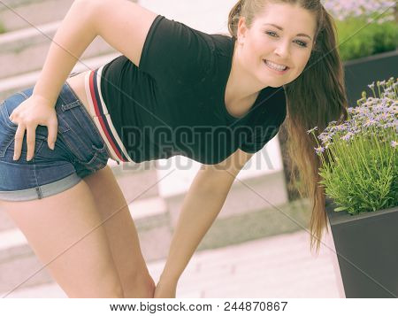 Close Up Of Happy Woman Smelling Wild Flowers. Female Being With Nature