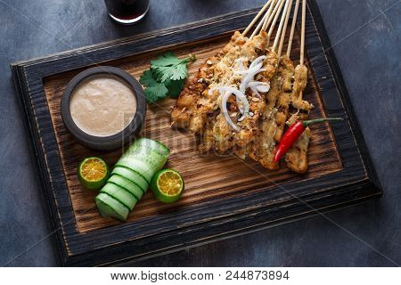 Close View Of Malaysian Chicken Skewers - Satay Or Sate Ayam With Peanut Sauce, Dark Background.