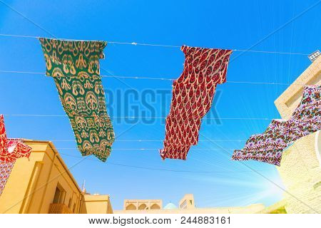 Waving In Sky Fabric. Multicolored Silk Textile Materials Fluttering Against The Blue Sky. Garland O