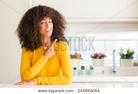 African american woman wearing yellow sweater at kitchen cheerful with a smile of face pointing with hand and finger up to the side with happy and natural expression on face looking at the camera.