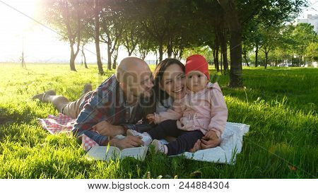 Happy Family Having A Rest And Kissing In The Nature With The Child At Sunset In The Park. Father Ki