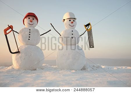 Snowman Builders. Christmas Or Xmas Decoration. New Year Snowman From Snow With Saw. Building And Re