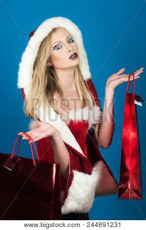 Santa Woman Wearing Santa Hat Holding Red Shopping Bags. Beautiful And Sexy Woman Dressed Santa Clau