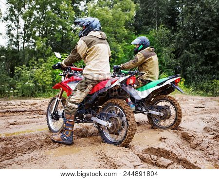 Motocross Racers Racing On The Off-road Circuit Mud Flying Through Air. Motorbike Through The Mud Wi