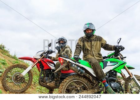 Two Mens Wearing Motorcycle Helmet And Safety Uniform Sitting On A Dirt Bike Outdoors, Beautiful Sce