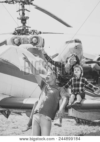 Family In The Aviation Museum. Mother, Father And Excited Child Sit On Planes Wing In Aviation Museu